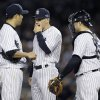 Photo -   New York Yankees manager Joe Girardi, middle, talks to pitcher Hiroki Kuroda, left, and Russell Martin in the eighth inning of Game 2 of the American League championship series against the Detroit Tigers Sunday, Oct. 14, 2012, in New York. (AP Photo/Matt Slocum)