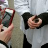 Pastor Emily Mellott, of the Calvary Episcopal Church in Lombard, Ill. ,takes a close up photo of ashes given to commuters at the Lombard train station on Wednesday, Feb. 22, 2012. (AP Photo/Daily Herald, Daniel White) MANDATORY CREDIT, MAGS OUT, TV OUT