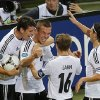 Germany\'s Lukas Podolski, second left, is celebrated by, from left, Mario Gomez, Philipp Lahm and Mesut Oezil after scoring the opening goal during the Euro 2012 soccer championship Group B match between Denmark and Germany in Lviv, Ukraine, Sunday, June 17, 2012. (AP Photo/Michael Probst)