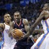 Atlanta Hawks guard Jeff Teague, center, drives between Oklahoma City Thunder guard Russell Westbrook (0) and center Kendrick Perkins (5) during the second quarter of an NBA basketball game in Oklahoma City, Sunday, Nov. 4, 2012. (AP Photo/Sue Ogrocki)