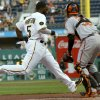Pittsburgh Pirates\' Josh Harrison (5) dashes home to score as Baltimore Orioles catcher Caleb Joseph waits for the relay throw in the first inning of the baseball game on Wednesday, May 21, 2014, in Pittsburgh . (AP Photo/Keith Srakocic)