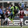Photo - Seattle Sounders' Obafemi Martins, second from right, and Djimi Traore (18) try to head the ball as Colorado Rapids goalkeeper Clint Irwin, left, and defender Drew Moor (3) look on, Saturday, April 26, 2014, in the first half of an MLS soccer match in Seattle. (AP Photo/Ted S. Warren)