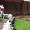 Clarice Block, 10, struggles as she carries a heavy sandbag down the sidewalk to help her neighbors, P.D. and Aleta Ritchey, sandbag their backyard on Joan Avenue to protect their house after their backyard was flooded from Pigeon Creek in Evansville, Ind. on Wednesday, April 27, 2011. Myra Taber, the Ritchey