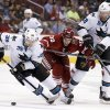 Photo - San Jose Sharks' Logan Couture, left, controls the puck as Phoenix Coyotes' Brandon Gormley (33) runs into Shark's Patrick Marleau (12) during the first period of an NHL hockey game on Saturday, April 12, 2014, in Glendale, Ariz. (AP Photo/Ross D. Franklin)