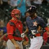 Photo - Rojos del Aguila de Veracruz catcher Humberto Sosa, left, watches as Houston Astros' Dexter Fowler crossed the plate after a solo home run in the fourth inning in a spring exhibition baseball game on Saturday, March 29, 2014, in Houston. (AP Photo/Richard Carson)