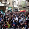 This citizen journalism image provided by Aleppo Media Center AMC which has been authenticated based on its contents and other AP reporting, shows anti Syrian regime protesters chanting slogans and waving the Syrian revolutionary flag during a demonstration, in Aleppo, Syria, Friday, April 19, 2013. Gunmen killed a government official in a Damascus restaurant, Syrian state media and activists reported Friday as regime troops and rebels fought fierce battles near the Lebanese border.(AP Photo/Aleppo Media Center, AMC)