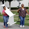 Shaketta Khalid carries a toddler\'s bed frame and her friend, Josie Ford, carries a floor lamp as the two leave a giant