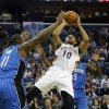 Photo - New Orleans Pelicans shooting guard Eric Gordon (10) shoots over Orlando Magic power forward Glen Davis (11) in the first half of an NBA basketball game in New Orleans, Sunday, Jan. 26, 2014. (AP Photo/Bill Haber)