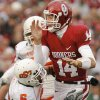 Oklahoma\'s Sam Bradford (14) takes a hit by Oklahoma State\'s Ricky Price (6) during the first half of the college football game between the University of Oklahoma Sooners (OU) and the Oklahoma State University Cowboys (OSU) at the Gaylord Family-Memorial Stadium on Saturday, Nov. 24, 2007, in Norman, Okla. Photo By NATE BILLINGS, The Oklahoman