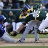 Photo - Oakland Athletics catcher Chris Gimenez, right, leaps past Texas Rangers' Jose Felix, center, as he tags out Alex Castellanos, left, caught trying to steal home during the eighth inning of a spring training baseball game Saturday, March 1, 2014, in Phoenix. (AP Photo/Gregory Bull)