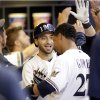 Photo - Milwaukee Brewers' Ryan Braun, center, celebrates with teammate Carlos Gomez (27) after hitting a two-run home run against the Pittsburgh Pirates during the first inning of a baseball game Friday, Aug. 22, 2014, in Milwaukee. (AP Photo/Darren Hauck)