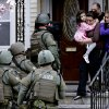 FILE - In this Friday, April 19, 2013 file photo, a woman carries a girl from their home as a SWAT team searching for a suspect in the Boston Marathon bombings enters the building in Watertown, Mass. Two suspects in the Boston Marathon bombing killed an MIT police officer, injured a transit officer in a firefight and threw explosive devices at police during their getaway attempt in a long night of violence that left one of them dead and another captured. Since Monday, Boston has experienced five days of fear, beginning with the marathon bombing attack, an intense manhunt and much uncertainty ending in the death of one suspect and the capture of the other. (AP Photo/Charles Krupa, File)