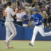 Toronto Blue Jays\' Jose Bautista, right, gestures to Baltimore Orioles pitcher Darren O\'Day after hitting a home run during the eighth inning of a baseball action in Toronto, Saturday June 22, 2013. (AP Photo/the Canadian Press, Chris Young)