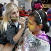 Volunteer Kerstie Moran paints a lion\'s face on Alexa Rojo, 11, Wednesday at the Sam Noble Oklahoma Museum of Natural History\'s Eggstravaganza in Norman. PHOTO BY STEVE SISNEY, THE OKLAHOMAN STEVE SISNEY