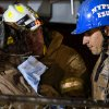 A worker, with black fire helmet at left, is rescued from an MTA subway construction project in New York early Wednesday, March 20, 2013 after being trapped up to his chest in debris for several hours. Fire officials say he is awake and conscious and is being evaluated at a local hospital. (AP Photo/Craig Ruttle)
