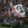 "Photo - The remains of the Portuguese soccer player legend Eusebio are carried inside a car as supporters cheer during his memorial tribute at the Benfica's Luz stadium in Lisbon, Monday, Jan. 6, 2014.  Eusebio, the Portuguese football star who was born into poverty in Africa but became an international sporting icon and was voted one of the 10 best players of all time, has died aged 71, his longtime club Benfica said. Few supporters hold posters with the photograph of Esusebio that read in Portuguese: ""Bye King"". (AP Photo/Francisco Seco)"