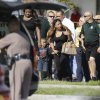 Photo - Parents with their children are escorted away with Orange County deputies after a vehicle crashed into a day care center, Wednesday, April 9, 2014, in Winter Park, Fla. At least 15 people were injured, including children. (AP Photo/John Raoux)