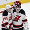 Photo - New Jersey Devils goalie Martin Brodeur (30) gets a hug from teammate Anton Volchenkov after defeating the Montreal Canadiens 4-1 in National Hockey League action, Tuesday, Jan. 14, 2014, in Montreal. (AP Photo/The Canadian Press, Ryan Remiorz)