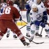 Photo - Vancouver Canucks' Zack Kassian (9) passes the puck past Phoenix Coyotes' Michael Stone (26) during the first period of an NHL hockey game on Tuesday, March 4, 2014, in Glendale, Ariz. (AP Photo/Ross D. Franklin)