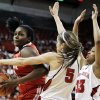 Ohio State\'s Darryce Moore, left, drives on Nebraska\'s Kaitlyn Burke (5) and Rebecca Woodberry (33) in the first half of their NCAA college basketball game in Lincoln, Neb., Sunday, Feb. 26, 2012. (AP Photo/Nati Harnik)