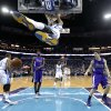 Photo - New Orleans Hornets forward Anthony Davis hangs from the rim after slam dunking over Sacramento Kings forward John Salmons (5) and guard Jimmer Fredette (7) in the first half of an NBA basketball game in New Orleans, Sunday, Feb. 24, 2013. (AP Photo/Gerald Herbert)