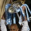 Photo - Manchester City's captain Vincent Kompany holds the trophy as the team celebrate in the city centre the day after they won the English Premier League title, in Manchester, England, Monday May 12, 2014. (AP Photo/Jon Super)