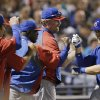 Photo - Chicago Cubs' Mike Olt is congratulated after hitting a solo home run during the second inning of a spring exhibition baseball game against the Seattle Mariners Wednesday, March 12, 2014, in Peoria, Ariz. (AP Photo/Darron Cummings)