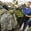 Mark Loeffler, owner, Brigadoon Military Surplus, holding a U.S. Army ALICE pack next to uniforms at Brigadoon Military Supply, 1805 S Sunnylane, in Del City Wednesday, Sept. 17, 2008. BY PAUL B. SOUTHERLAND, THE OKLAHOMAN