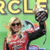 Funny Car driver Courtney Force raises one of her trophies for being the 100th professional win for women drivers in the NHRA after defeating Cruz Pedregon in the finals at Heartland Park in Topeka, Kan., on Sunday May 25, 2014. (AP Photo/The Topeka Capital Journal, Chris Neal)