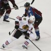 Photo - Chicago Blackhawks center Michal Handzus, front, of Slovakia, picks up a loose puck as Colorado Avalanche defenseman Nick Holden covers in the first period of an NHL hockey game in Denver on Wednesday, March 12, 2014. (AP Photo/David Zalubowski)