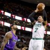 Photo - Boston Celtics center Jared Sullinger (7) shoots over Sacramento Kings center DeMarcus Cousins during the first half of an NBA basketball game on Friday, Feb. 7, 2014, in Boston. Sullinger scored 31 points in the Celtics' 99-89 win. (AP Photo/Mary Schwalm)