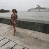 A Filipino\'s hair blows in the strong winds from Typhoon Koppu as she walks along the promenade where a barge and passenger boat are seen drifting close to shore by strong currents in Manila Bay, Philippines, on Monday, Oct. 19, 2015. Army, police and civilian volunteers scrambled Monday to rescue hundreds of villagers trapped in their flooded homes and on rooftops in a northern Philippine province battered by slow-moving Typhoon Koppu. (AP Photo/Aaron Favila)
