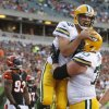 Green Bay Packers quarterback Aaron Rodgers (12) is lifted in the air by offensive tackle T.J. Lang (70) after Rodgers ran for a touchdown in the first half of an NFL preseason football game against the Cincinnati Bengals, Thursday, Aug. 23, 2012, in Cincinnati. Bengals defensive end Michael Johnson is at left. (AP Photo/David Kohl)