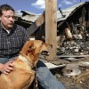 Photo - Walt Harmon, 24, sits with his dog, Pal, a mutt, at the back of what's left of his family's home Tuesday afternoon, July 19, 2011. The dog awakened Walt's mother,  Susan Harmon with constant barking Sunday night when their home caught fire. Walt credits the pet with saving his life and allowing him to rescue his mother, and her parents, Harold and Donna Gilliam.  from the smoke-filled home before it was destroyed by flames.   The home is in rural Lincoln County about six miles north of Jacktown.     Photo by Jim Beckel, The Oklahoman