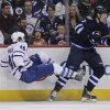 Photo - Winnipeg Jets' Keaton Ellerby (7) checks Toronto Maple Leafs' Troy Bodie (40) during the second period of an NHL hockey game Saturday, Jan. 25, 2014, in Winnipeg, Manitoba. (AP Photo/The Canadian Press, Jason Woods)
