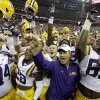 Photo - LSU coach Les Miles, center, is surrounded by his team as they celebrate beating Wisconsin in an NCAA college football game Saturday, Aug. 30, 2014, in Houston. LSU won 28-24. (AP Photo/David J. Phillip)