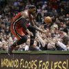 Miami Heat\'s LeBron James jumps onto a table while trying to save a ball going out of bounds against the Milwaukee Bucks in the second half of an NBA basketball game Friday, March, 15, 2013, in Milwaukee. (AP Photo/Jeffrey Phelps)