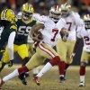 Photo - San Francisco 49ers quarterback Colin Kaepernick (7) runs against Green Bay Packers defense during the first half of an NFL wild-card playoff football game, Sunday, Jan. 5, 2014, in Green Bay, Wis. (AP Photo/Jeffrey Phelps)