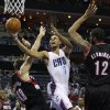 Charlotte Bobcats\' Ramon Sessions (7) drives between Portland Trail Blazers\' Joel Freeland (19) and LaMarcus Aldridge (12) during the first half of an NBA basketball game in Charlotte, N.C., Monday, Dec. 3, 2012. (AP Photo/Chuck Burton)