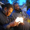 File - In this Nov. 6, 2013 file photo Charles Hannah lights Theresa Walker\'s candle, left, at a vigil for Renisha McBride in the front of the home where she was shot in Dearborn Heights, Mich. Prosecutors plan to announce Friday, Nov. 15, 2013 whether they\'ll charge a suburban Detroit homeowner in the shooting death of McBride. Autopsy results released after the shooting ruled McBride died of a gunshot wound to her face. (AP Photo/Detroit News, Ricardo Thomas, File) DETROIT FREE PRESS OUT; HUFFINGTON POST OUT