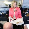 Ann Romney, wife of Republican presidential candidate and former Massachusetts Gov. Mitt Romney, hands out pastry to reporters on the plane after a campaign event at Portsmouth International Airport, in Newington, N.H., Saturday, Nov. 3, 2012. (AP Photo/Charles Dharapak)