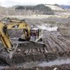 An excavator clears a drainage channel at the scene of a deadly mudslide, torn loose from the hillside at upper right, Wednesday, April 2, 2014, in Oso, Wash. The March 22 mudslide has killed at least 29 and another 13 are unaccounted for. (AP Photo/Elaine Thompson)