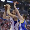 Photo - Los Angeles Clippers forward Blake Griffin, left, shoots around Golden State Warriors forward David Lee during the first half in Game 2 of an opening-round NBA basketball playoff series in Los Angeles, Monday, April 21, 2014. (AP Photo/Chris Carlson)