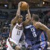 Photo - Milwaukee Bucks' Brandon Knight (11) drives between Charlotte Bobcat defenders Michael Kidd-Gilchrist and Kemba Walker (15) during the second half of an NBA basketball game on Sunday, March 16, 2014, in Milwaukee. (AP Photo/Tom Lynn)