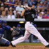 Photo - Colorado Rockies' Justin Morneau, right, follows the flight of his triple with Chicago Cubs catcher Wellington Castillo in the fourth inning of a baseball game in Denver on Wednesday, Aug. 6, 2014. (AP Photo/David Zalubowski)