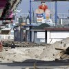 Photo - FILE - In this Nov. 22, 2012 file photo, a woman walks past debris from the damaged boardwalk in Seaside Heights, N.J. The iconic boardwalk where generations of families and teens got their first taste of the Jersey Shore and where the reality show of the same name was filmed is being rebuilt following its destruction in Superstorm Sandy. Seaside Heights on Wednesday, Jan. 16, 2013 awarded a $3.6 million contract to have the boardwalk rebuilt in time for Memorial Day weekend.  (AP Photo/Mel Evans, File)