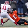 Oklahoma\'s Lacoltan Bester (11) cuts back on a tackle attempt by Oklahoma State\'s Daytawion Lowe (8) during the Bedlam college football game between the Oklahoma State University Cowboys (OSU) and the University of Oklahoma Sooners (OU) at Boone Pickens Stadium in Stillwater, Okla., Saturday, Dec. 7, 2013. Photo by Chris Landsberger, The Oklahoman
