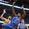 Photo - Oklahoma City Thunder's Andre Roberson, front, shoots around Cleveland Cavaliers' Spencer Hawes during the first quarter of an NBA basketball game Thursday, March 20, 2014, in Cleveland. (AP Photo/Tony Dejak)