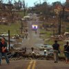 People walk down a street lined with destroyed homes in Joplin, Mo., Sunday, May 22, 2011. A large tornado moved through much of the city, damaging a hospital and hundreds of homes and businesses. (AP Photo/Mark Schiefelbein) ORG XMIT: MOMS101