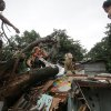 Residents and rescuers cut up a fallen tree on top of damaged a house from Typhoon Koppu in suburban Quezon city, north of Manila, Philippines on Monday, Oct. 19, 2015. Army, police and civilian volunteers scrambled Monday to rescue hundreds of villagers trapped in their flooded homes and on rooftops in a northern Philippine province battered by slow-moving Typhoon Koppu. (AP Photo/Aaron Favila)